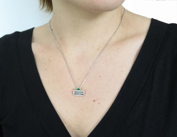Collier porté orné d'une chaîne en argent orné d'un pendentif géométrique en emeraude