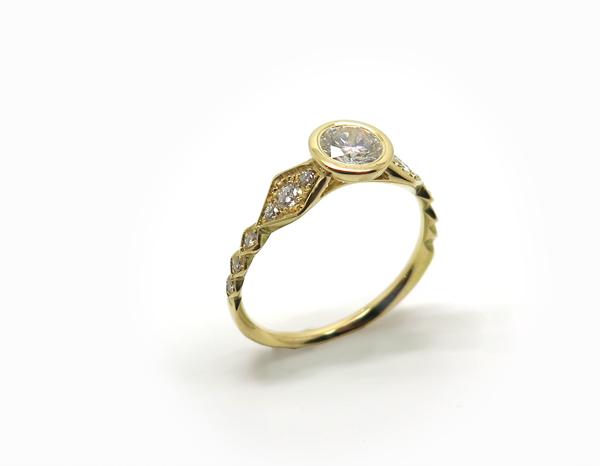 Solitaire en or jaune dont le corps de bague est très travaillé et pavé de diamants
